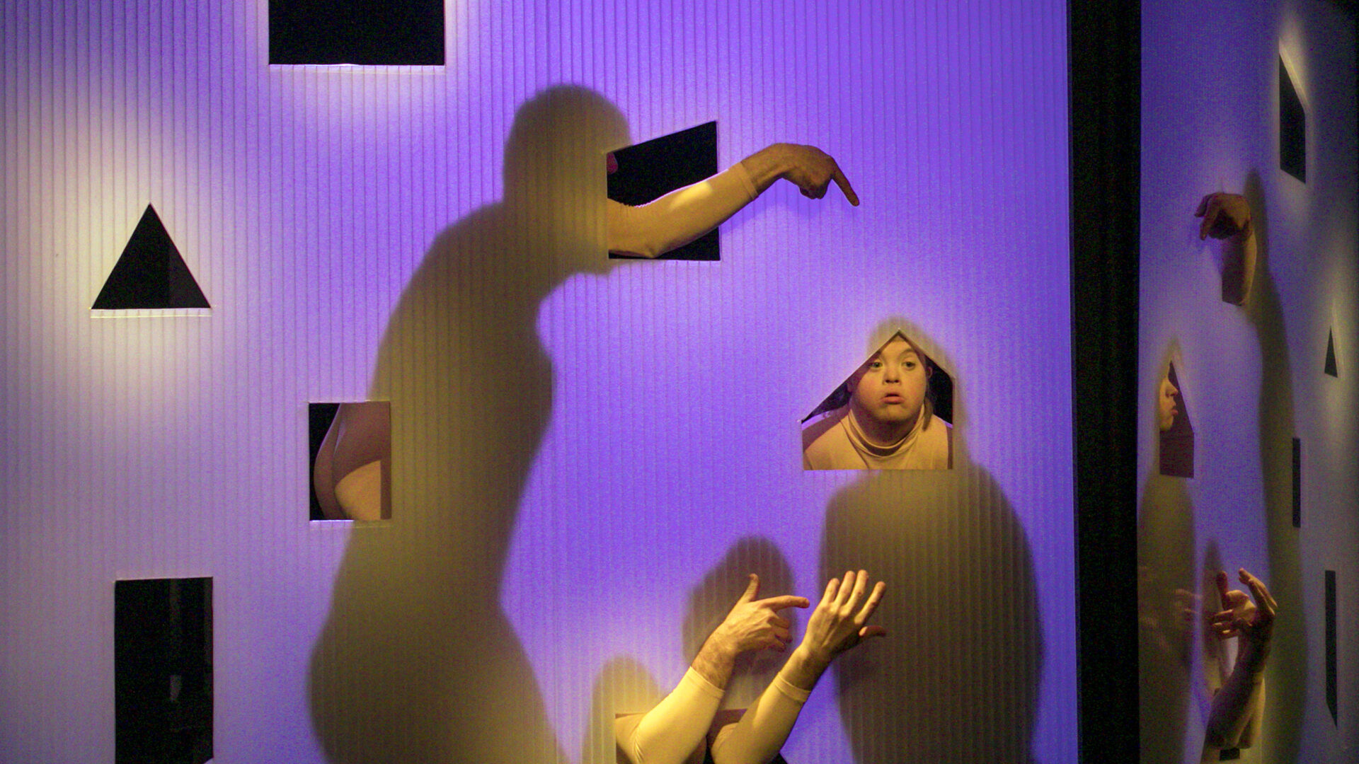 scene photo of a performance: shadows of three people behind a transparent wall on a theatre stage. Some body parts are visible.