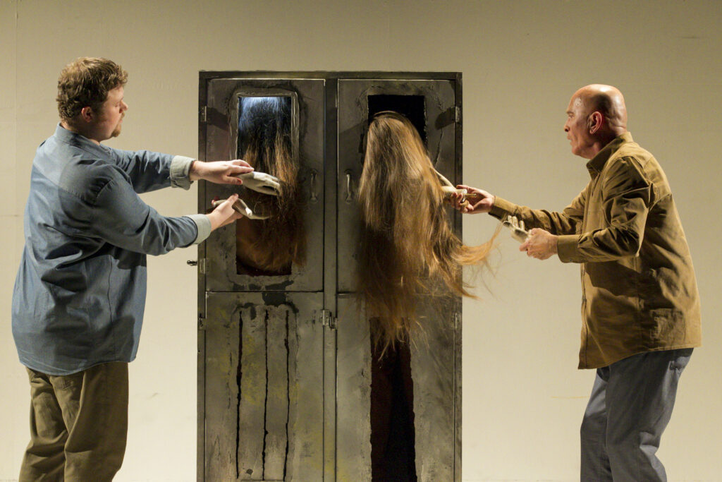 Scene photo of a performance: A metal cupboard on a stage. One men to the left one man to the right with plastic hands. Hair is hanging out of the metal cupboard, which is touched by the hands.