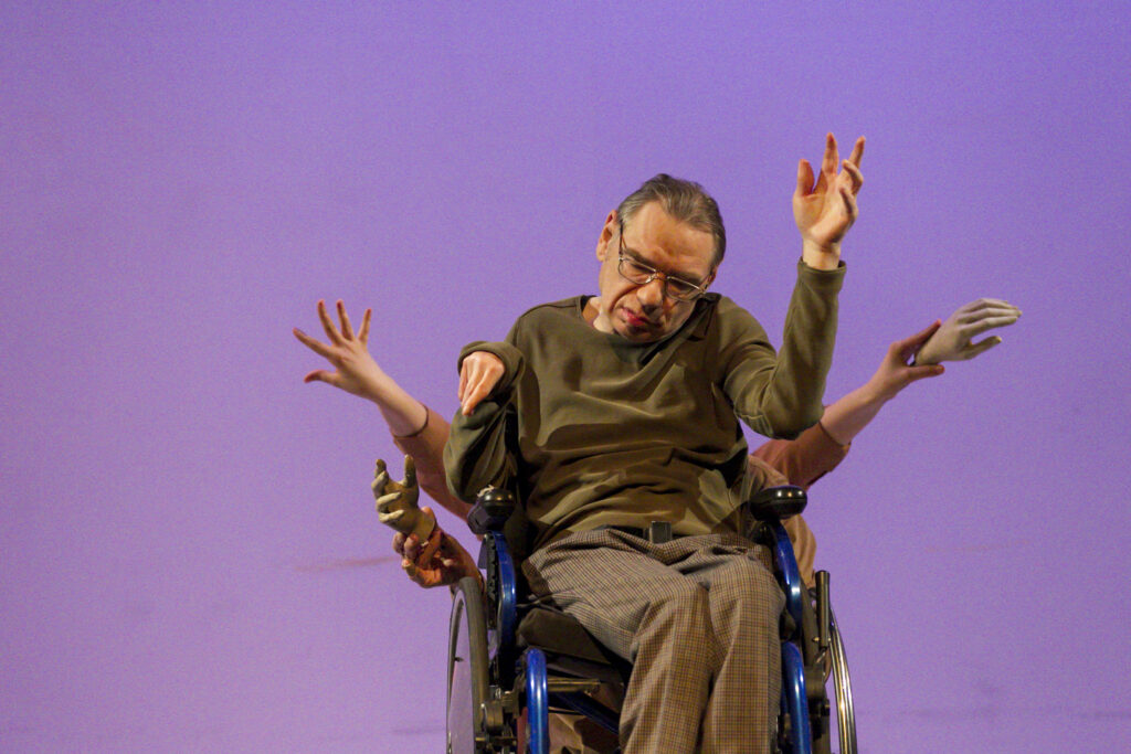 Scene photo of a performance: A man in a wheelchair on a stage. Other people are being him. But you just see their hands.