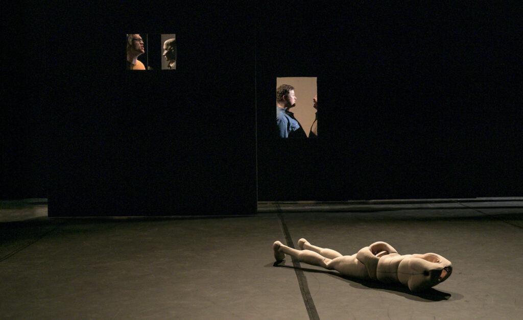 Szenenfoto einer Auffuehrung: eine Puppe ohne Kopf liegt auf einer Buehne. Dahinter in kleinen Fenstern Schauspieler*innen.