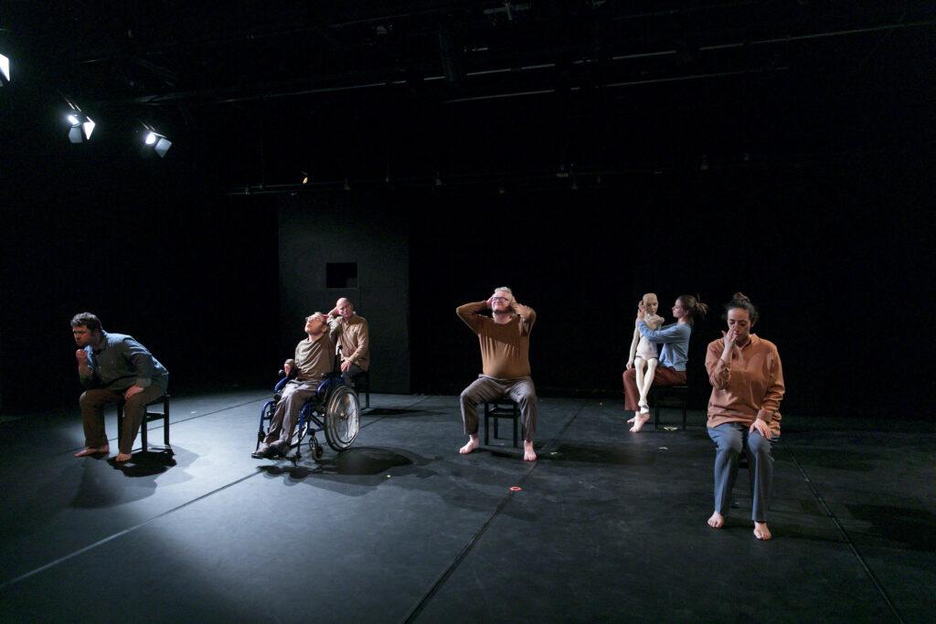 Szenenfoto einer Auffuehrung: Mehrere Performer*innen sitzen auf Hockern auf einer Buehne.