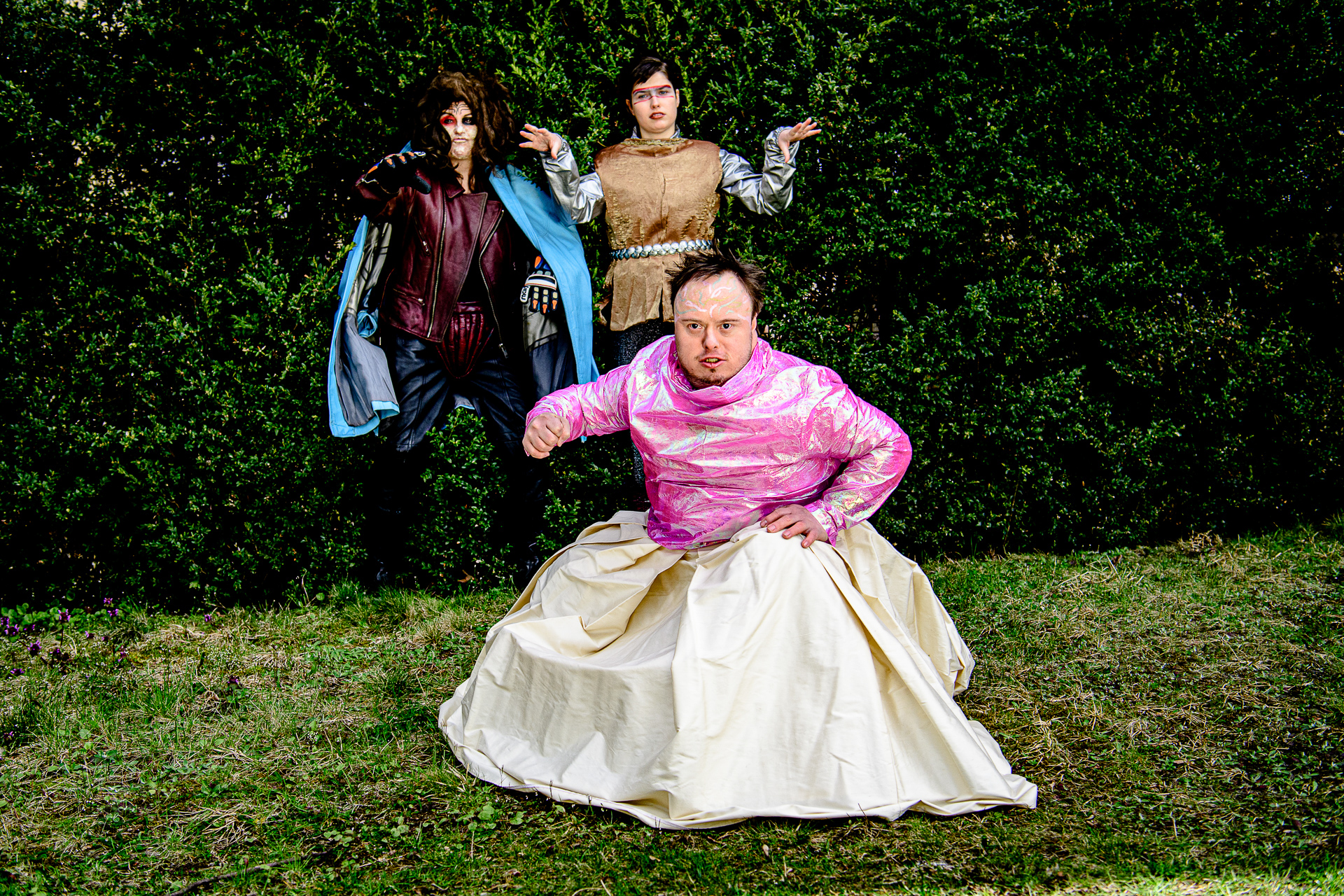 Drei Performer:innen in Kostuemen auf einer Wiese vor einer Hecke