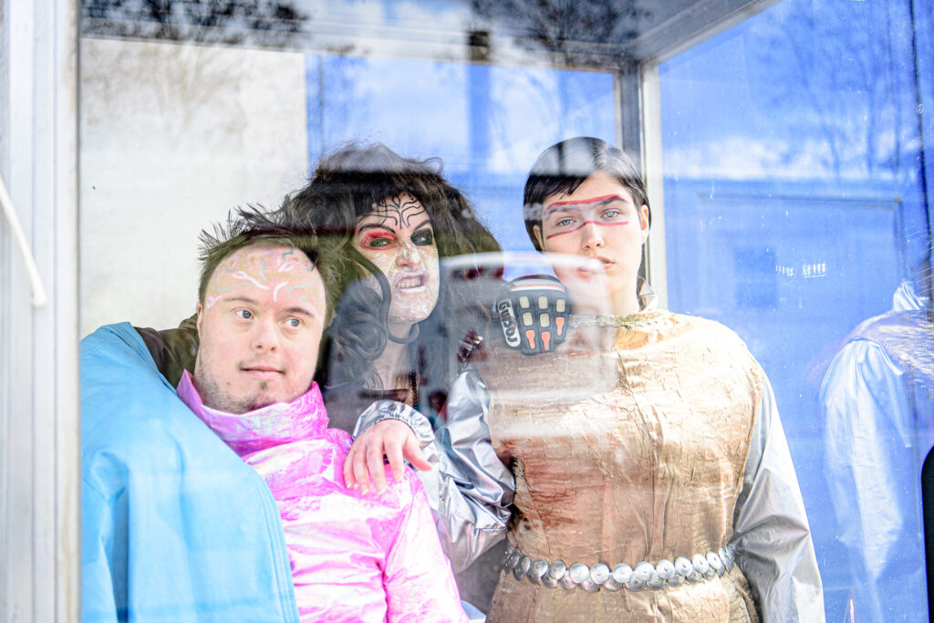 Three actors with costumes in a glasbox
