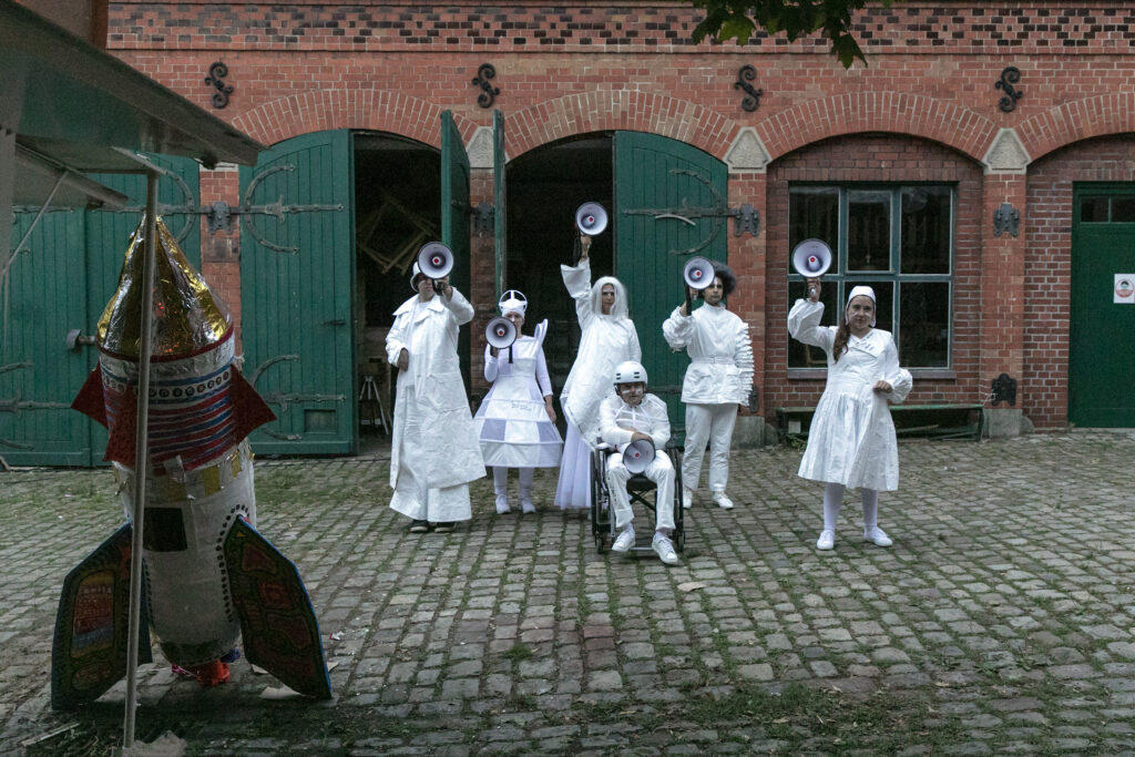 Szenenfoto einer Auffuehrung: Mehrere Personena uf einer Buehne in weissen Kostümen mit Megafonen. Links eine Rakete auf Pappe.