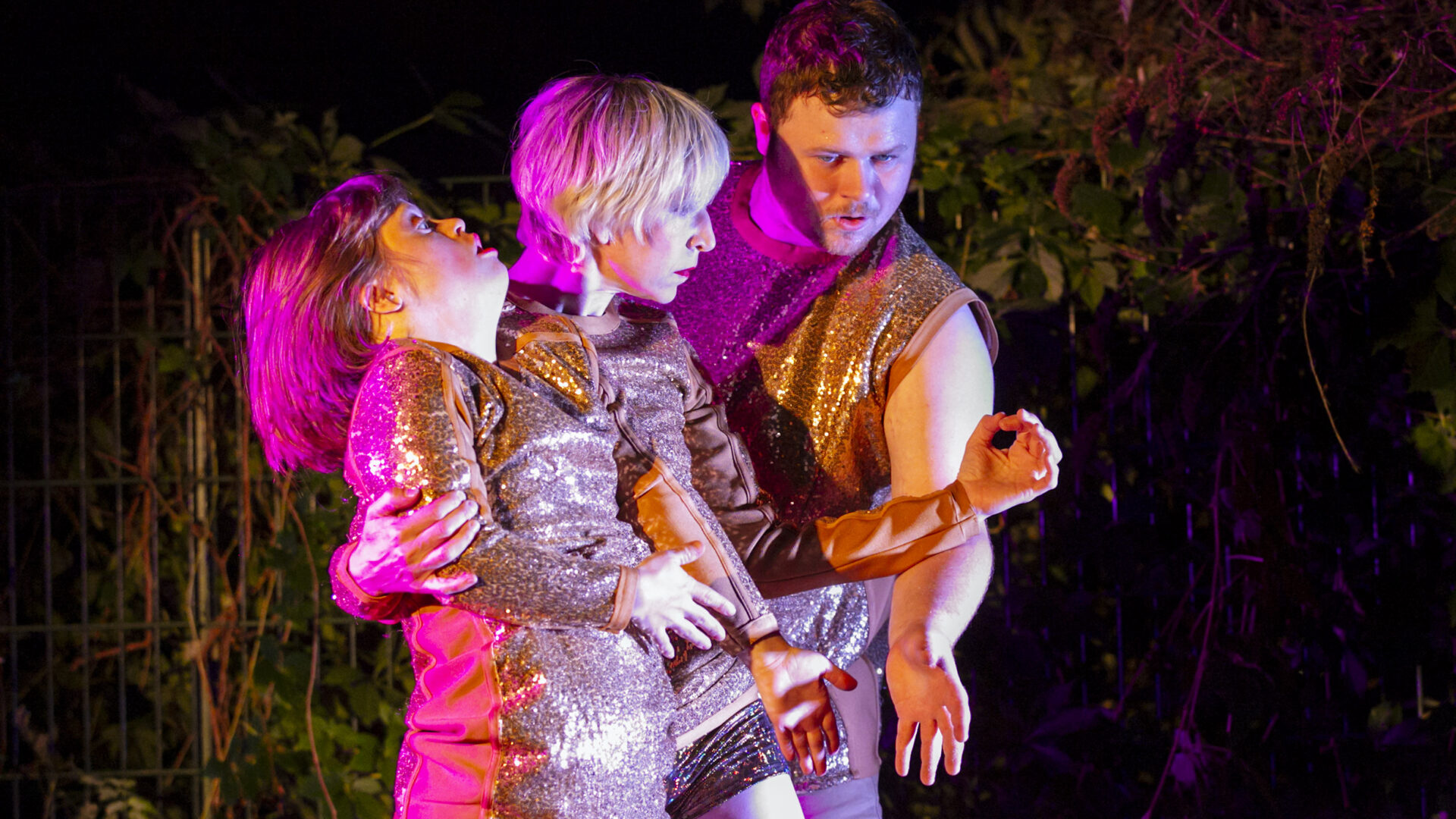 Scene photo of a performance: Three people in glitter costumes dancing on a stage.