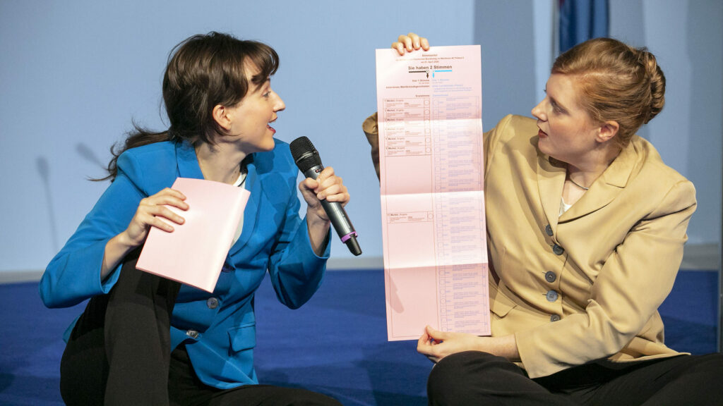 Szenenfoto einer Auffuehrung: Zwei Performerinnen mit einem Wahlzettel auf einer Buehne.