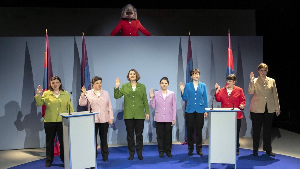 Szenenfoto einer Auffuehrung: Sieben Performerinnen in Anzuegen in der Mitte einer Person mit Adlermaske oben.