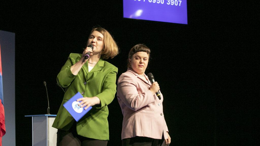 Szenenfoto einer Auffuehrung: Zwei Performerinnen mit Mikrofon. Im Hintergrund eine Telefonnummer auf einem Bildschirm.