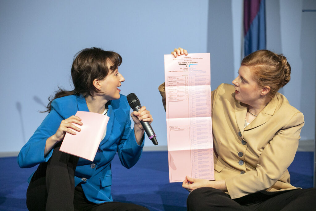 Scene photo of a performance: Two performers holding and looking at ballot paper on a stage.
