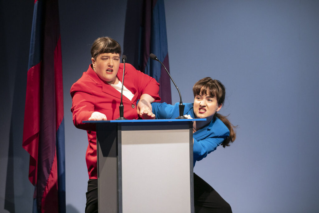 Scene photo of a performance: Two performers fighting over a lectern.