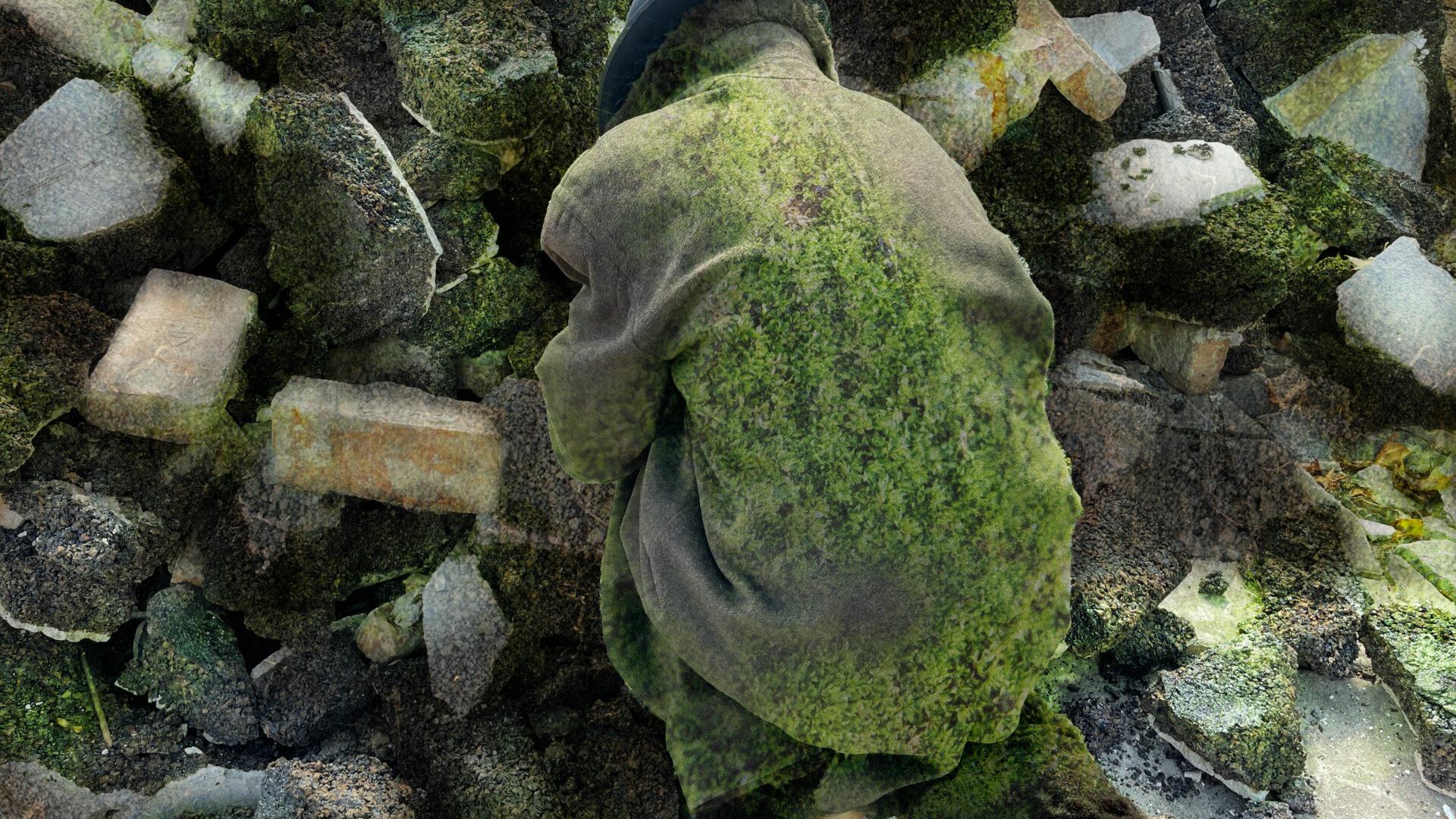 Szenenfoto einer Auffuehrung: Eine Person mit Filzmantel und Hut hockend vor einem Truemmerhaufen. Der Mantel und die Trümmer sind teilwese mit Moos bewachsen.