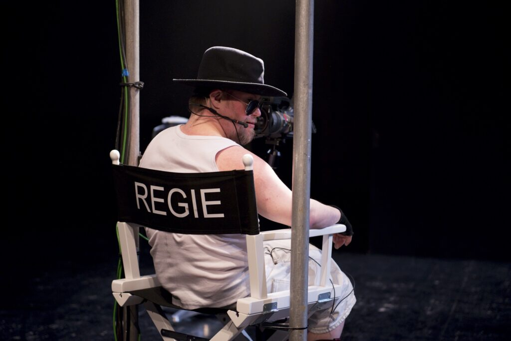 Scene photo of a performance: One man is sitting in a directors chair.