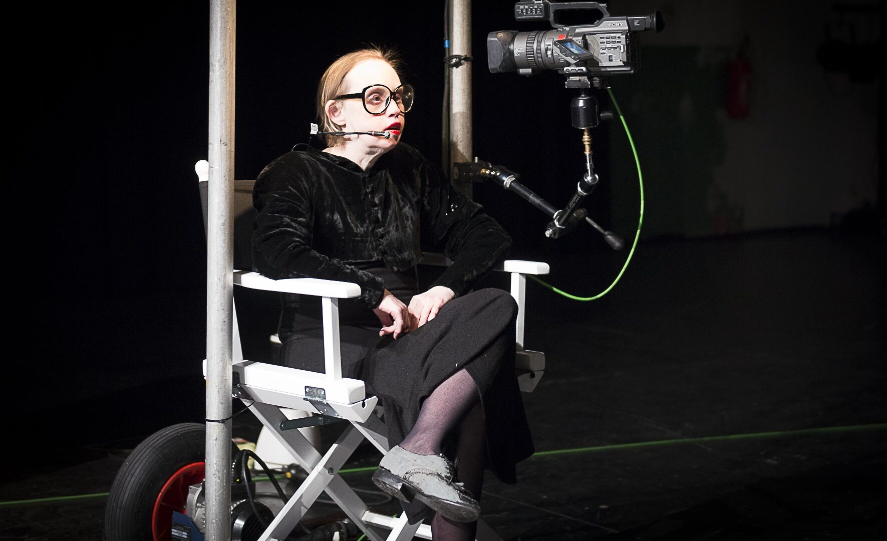 Scene photo of a performance: One woman is sitting in a directors chair.