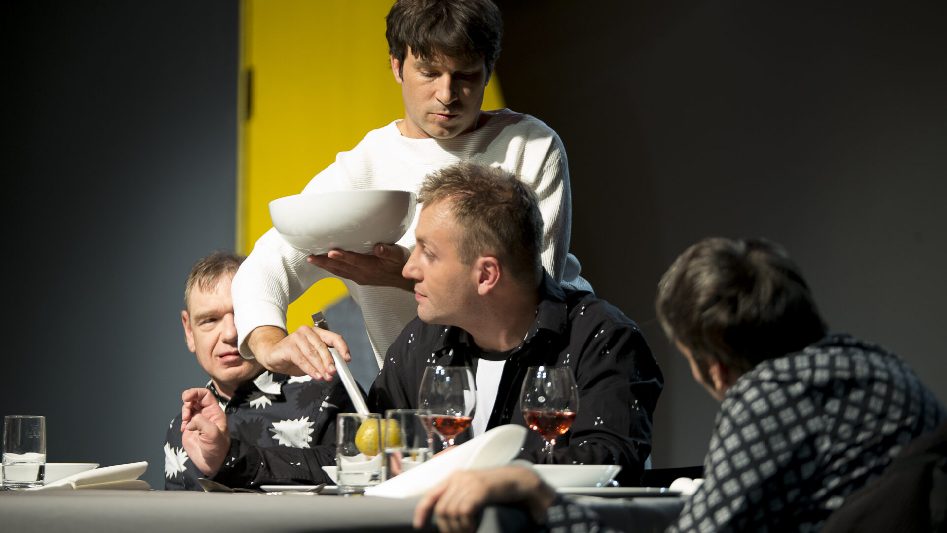 Szenenfoto einer Auffuehrung: drei Personen sitzen am Tisch ein einer Buehne. Einer steht zwischen den beiden ersten Personen von links und schenkt ein Getraenk ein.